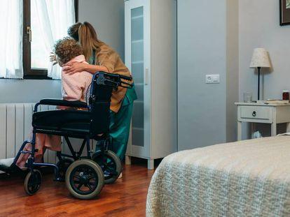 Una cuidadora acompaña a una anciana dependiente.