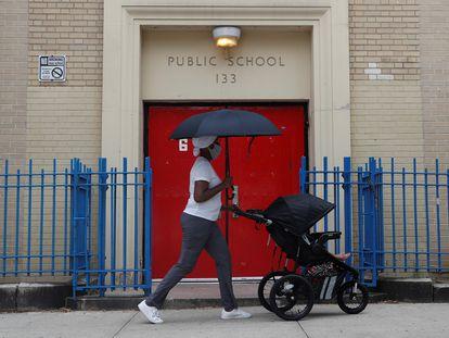 Una mujer camina frente a una escuela pública con su bebé, en Nueva York.