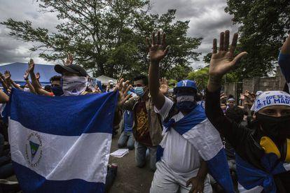 Un grupo de amigos y familiares rezan a la entrada de El Chipote, el centro donde son trasladados los detenidos durante las protestas.