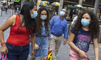 Several people with masks walk through Times Square, in New York, last Tuesday.