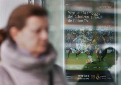Una mujer pasa frente a un anuncio de Fusión TV en una tienda de Telefónica Movistar.