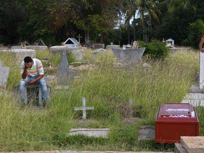 Un hombre en un cementerio donde fue enterrada una víctima del naufragio en Trinidad y Tobago.
