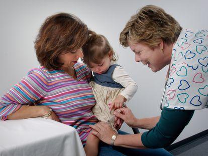 Una niña llora durante su vacunación.
