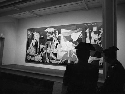 Agentes de la Guardia Civil vigilan la urna blindada que protege el 'Guernica', obra de Pablo Picasso, en su presentación en el emplazamiento del Casón del Buen Retiro de Madrid, tras su regreso a España.