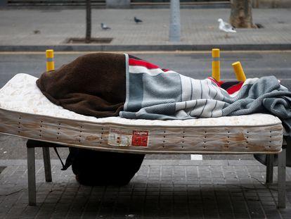 Una persona sin hogar descansa en un banco del barrio de Sant Andreu de Barcelona, el pasado viernes.