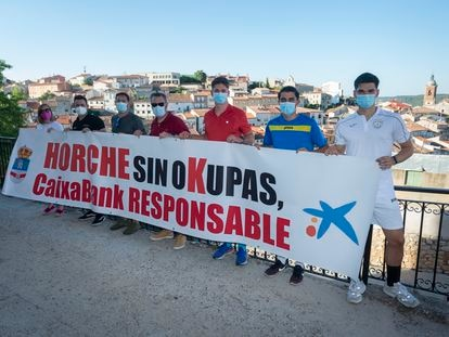 Varios vecinos de Horche posan con su pancarta contra los okupas del pueblo.