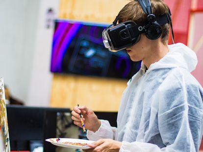Un joven pinta con unas gafas de realidad virtual.