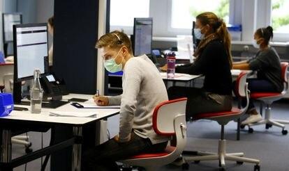 Varios trabajadores de un centro de atención al cliente hablan por teléfono.