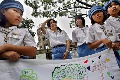 Varias colegialas llevan, como ya es habitual en la ciudad, una pancarta con mensajes de paz en el Parque Memorial de la Paz de Hiroshima. Detrás de ellas se levantan las ruinas del antiguo Salón Provincial de Exposiciones, milagroso superviviente de la bomba.