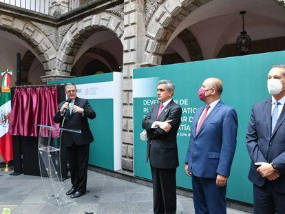 El secretrario de Relaciones Exteriores, Marcelo Ebrard, muestra una placa en honor a Simón Bolivar en Ciudad de México.