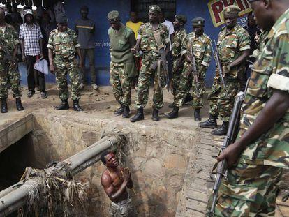Un presunto miembro de la milicia juvenil Imbonerakure del partido gobernante suplica a los soldados que lo protejan de una multitud de manifestantes en mayo de 2015 en Burundi.