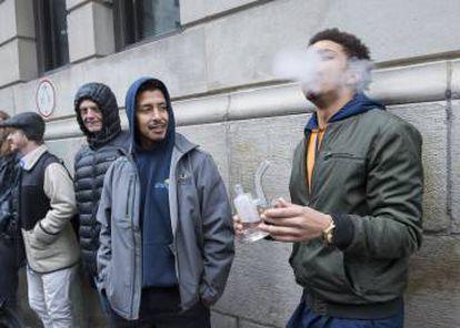 Un hombre fuma cannabis mientras espera en la cola de una tienda de marihuana en Montreal.