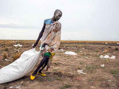 Una mujer arrastra un saco de comida lanzado desde el aire por el Programa Mundial de Alimentos en Ganyiel (Sudán del Sur).