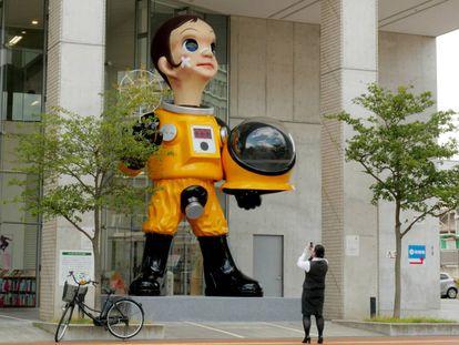 Una mujer toma una fotografía de la escultura gigante del niño con traje antirradiación, 'Sun Child', en Fukushima (Japón).