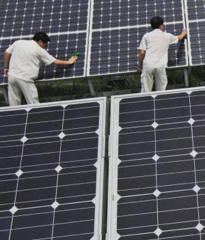 Un grupo de trabajadores chinos limpia unos paneles solares en Hebei, China.