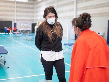 Begoña Arana habla con una mujer alojada en el pabellón para sin techo instalado en Algeciras.
