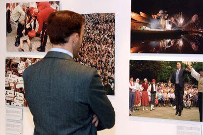 """Una persona observa varias fotografias que componen la exposición """"Efe, 75 años en fotos."""