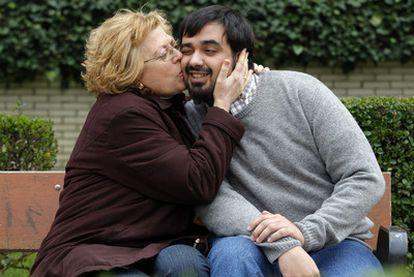 Carmen Rodríguez, en un jardín próximo a su casa de Leganés, besa a David, el hijo que adoptó en 1981 en la clínica San Ramón de Madrid.