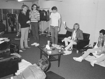 Parte del grupo Queen (Roger Taylor -con un vaso- Freddie Mercury - a la derecha- y Brian May -su melena a la izquierda-) en un concierto en Nishinomiya, Japón, en 1982. De pie, a la izquierda de la imagen (con un jersey oscuro y un vaso en la mano), Paul Prenter, mirando a Mercury.