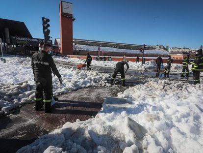 Militares de la UME realizan labores de limpieza para retirar la nieve en la Estación Puerta de Atocha, en Madrid, este lunes.