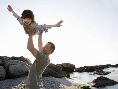 Un padre juega con su hijo en la playa.