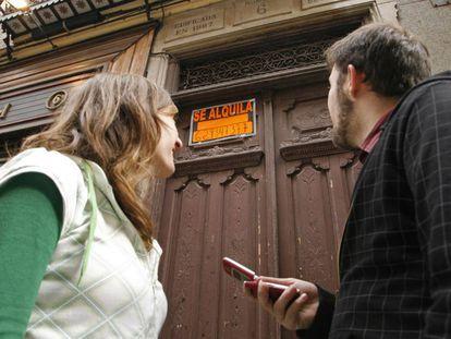 Dos jóvenes frente a un portal con un piso en alquiler.