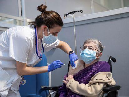 Una profesional sanitaria vacuna a una mujer durante la vacunación de los mutualistas de Muface, Isfas y Mugeju, en marzo en Madrid.