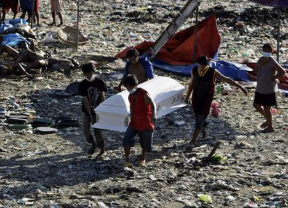 Cuatro hombres transportan un ataúd entre los cadáveres que han sido encontrados en varios lugares de la localidad filipina de Cayagan de Oro.