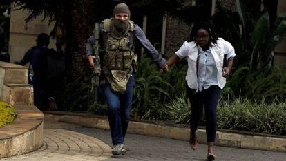 Un miembro de las fuerzas de seguridad kenianas evacúa a una mujer del hotel Dusit que fue atacado en Nairobi a mediados de enero.
