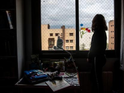 Una niña mira desde su ventana al exterior en Madrid, durante el confinamiento. ÁLVARO GARCÍA