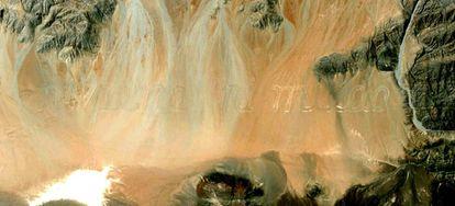 Frase horadada en el desierto de Atacama con un verso de Zurita.