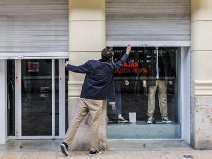 El propietario de un comercio cierra su establecimiento de Valencia el pasado jueves.