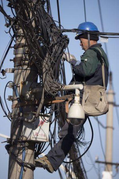 Ingenieros trabajan en postes de electricidad de Pekín (China).