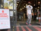 LARKSPUR, CALIFORNIA - APRIL 02: A customer walks by a now hiring sign at a BevMo store on April 02, 2021 in Larkspur, California. According to a report by the Bureau of Labor Statistics, the U.S. economy added 916,000 jobs in March and the unemployment rate dropped to 6 percent. Leisure and hospitality jobs led the way with 280,000 new jobs followed by restaurants with 176,000 jobs and construction with 110,000 new positions.   Justin Sullivan/Getty Images/AFP == FOR NEWSPAPERS, INTERNET, TELCOS & TELEVISION USE ONLY ==