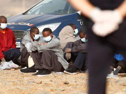 Un grupo de migrantes subsaharianos llegados en patera es vigilado por la policía nacional en la playa Aeroclub de la localidad de San Bartolome De Tirajana, en la isla de Gran Canaria, el 28 de agosto de 2020.