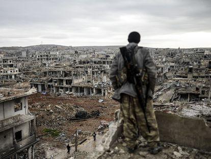 Un miliciano kurdo observa la aldea destruida de Halimce, al este de la ciudad siria de Kobane, en enero de 2015.
