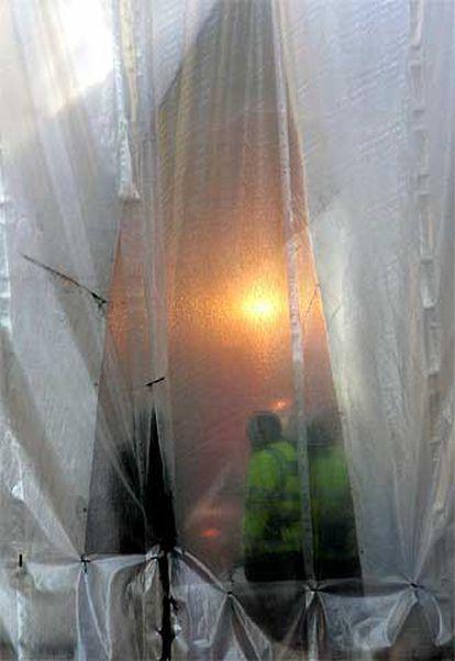 Un policía cierra la cortina utilizada para proteger de la vista el lugar donde el pasado 7 de julio estalló una bomba en un autobús. Según ha afirmado Scotland Yard, existen pruebas que confirman la muerte de uno de los terroristas suicidas durante los ataques.