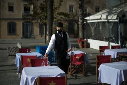 Un camarero prepara mesas en un restaurante de Barcelona.