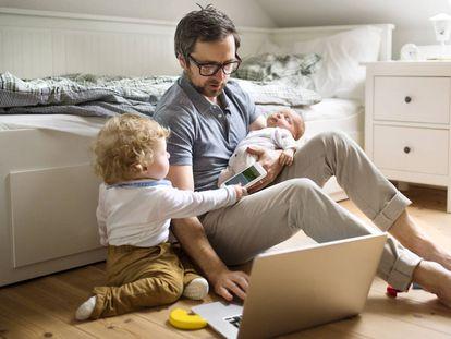 Un padre con dos niños mira un ordenador en su casa.