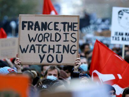 """""""Francia, el mundo te está mirando"""", dice un cartel en la manifestación el sábado en París contra la ley de seguridad de Macron."""