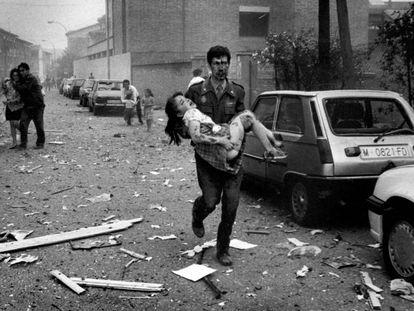 Un agente de la Guardia Civil ensangrentado lleva en brazos a una niña herida en el atentado contra la Casa Cuartel de Vic.