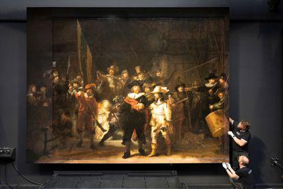 Dos trabajadores colocan la reconstrucción de los fragmentos de lienzo que se recortaron de 'La ronda de noche'.