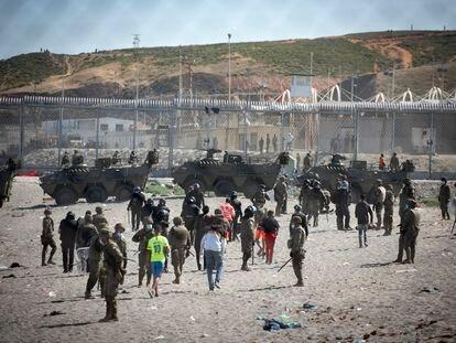 Un grupo de militares acompaña a varios inmigrantes llegados por mar a la playa ceutí del Tarajal, el pasado martes.