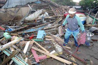 Un superviviente del <i>tsunami</i> inspecciona las ruinas de su casa.