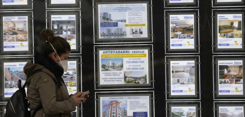 Una mujer pasa ante el escaparate de una inmobiliaria en Bilbao, durante el estado de alarma.