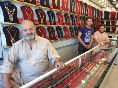 Mohsen Kayumi, con sus hijos, en la tienda de venta de oro de su propiedad, el jueves en Kabul (Afganistán).