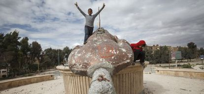 Unos niños en Raqqa juegan junto a los restos de una estatua de Basil El Asad, hermano del presidente.