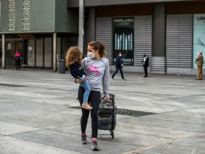 Una madre con mascarilla camina a casa con su hija en brazos después de hacer la compra, en la plaza de Felipe II (Madrid).