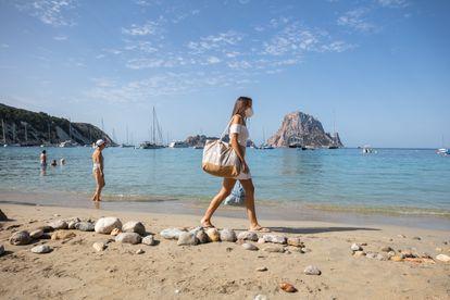 Una mujer pasea por Cala d'Hort (Ibiza).