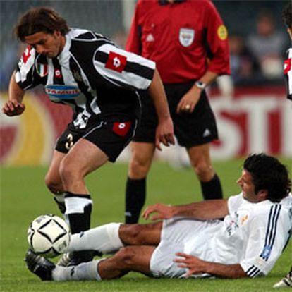Figo pugna por un balón con Tacchinardi en presencia del árbitro.